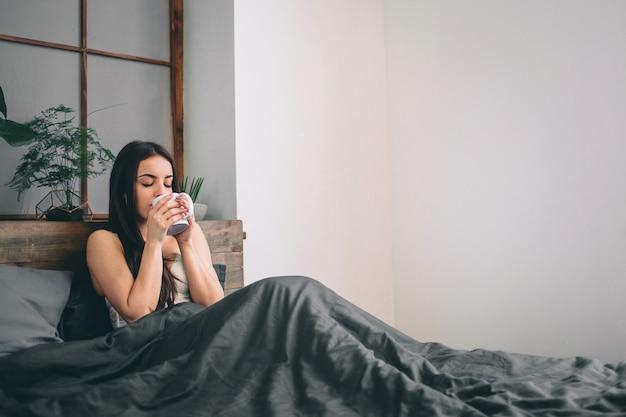 おはようございますベッドで目が覚めた女性ベッドでコーヒーを飲む女性