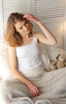 おはようございます!ベッドで目を覚ます若い美しい女性は、完全に休んだ。健康的な生活様式。スウィートホーム。