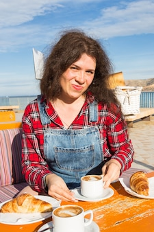 좋은 아침. 커피와 크로 해변 카페 테라스에서 야외에서 앉아 프랑스 아침 식사하는 젊은 여자.