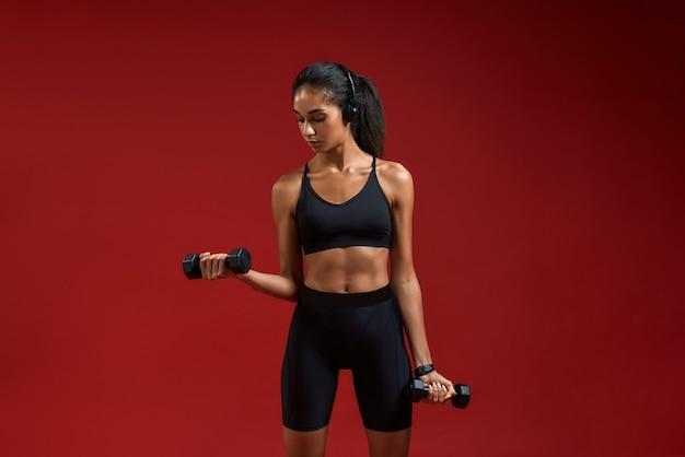 Хорошая музыка для тренировки красивой и спортивной молодой женщины в наушниках, тренирующейся с гантелями