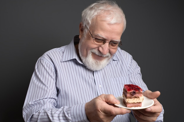 Good-natured smiling man  holding a plate and looking at the cake