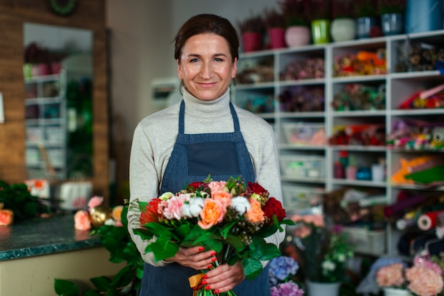 A good-natured woman florist stands in the middle of a flower shop with a bouquet of beautiful flowers