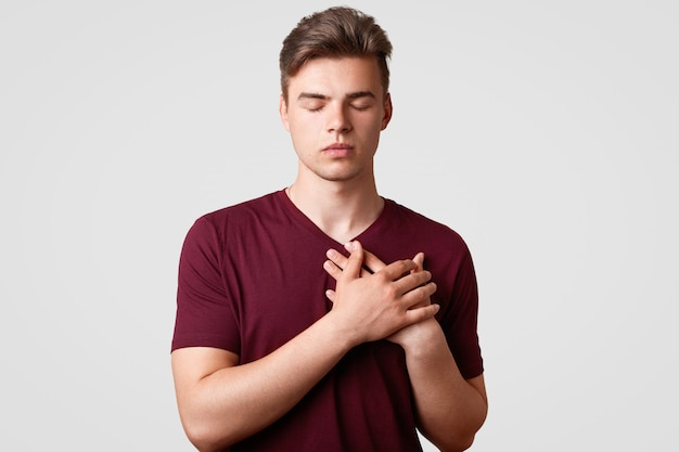 Good natured young hipster male with stylish haircut, keeps hands on heart, demonstrates his gratitude and kind manners, wears casual t shirt, isolated on white. thankfulness