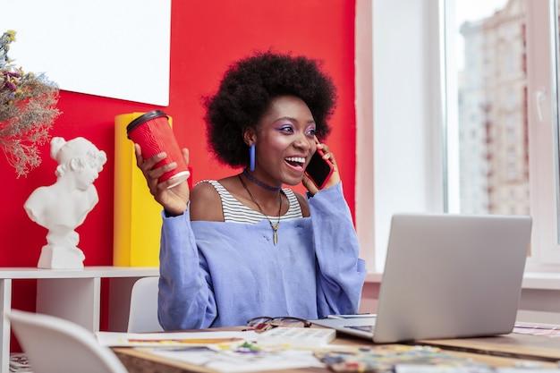 좋은 소식. 전화로 말하는 동안 좋은 소식을 듣고 기뻐하는 아프리카 계 미국인 디자이너