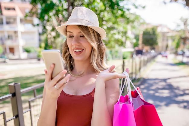 좋은 소식과 구매. 행복 한 십 대 소녀 구매 가방을 들고 전화를 보면서 웃 고. 스마트 폰에서 앱을 사용하여 메시지 읽기, 문자 메시지, 전화 번호