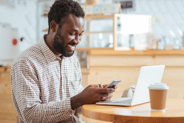Хорошие новости. очаровательный жизнерадостный мужчина сидит за столиком в кафе и читает текстовое сообщение от своих друзей, счастливо улыбаясь