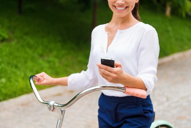 Хорошие новости от друзей. крупный план молодой женщины, держащей мобильный телефон и улыбающейся во время прогулки на велосипеде в парке