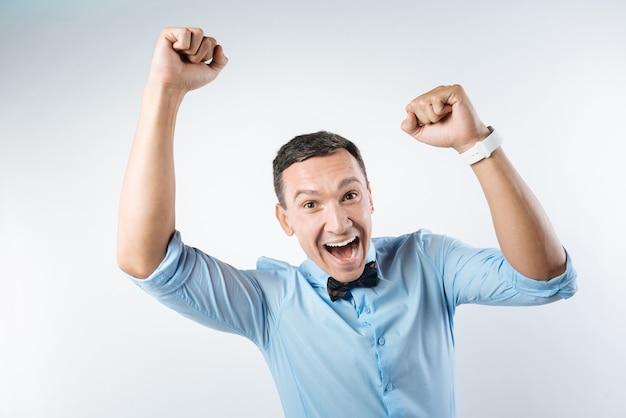 朗報です。彼らに圧倒されながら笑顔と彼の感情を示す幸せな楽観的な歓喜の男