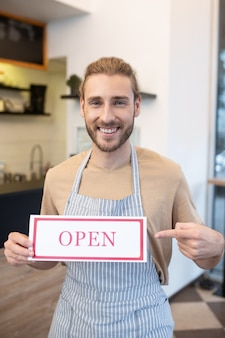 良いニュースです。カフェが開いていることを示すバーの近くに立っている縞模様のエプロンで幸せな若いひげを生やした男