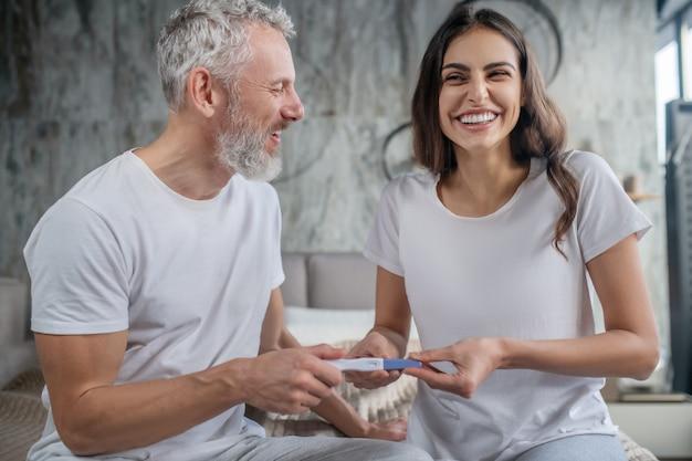 Хорошие новости. счастливая молодая длинноволосая женщина и взрослый седой мужчина, сидя на кровати с тестом на беременность