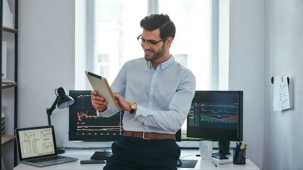 Good news happy young trader in formal wear is looking is using his digital tablet