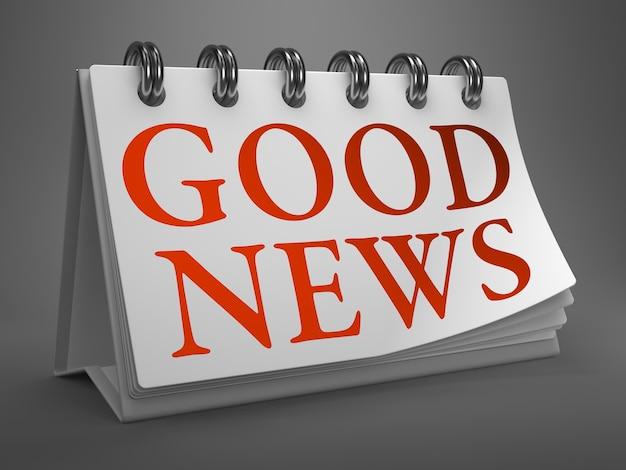 良いニュース-灰色の背景で隔離の白いデスクトップカレンダーの赤いテキスト。