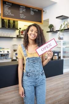良いニュースです。彼女の手でカフェで開いている碑文と看板を保持している長い黒髪の輝くムラートの女性