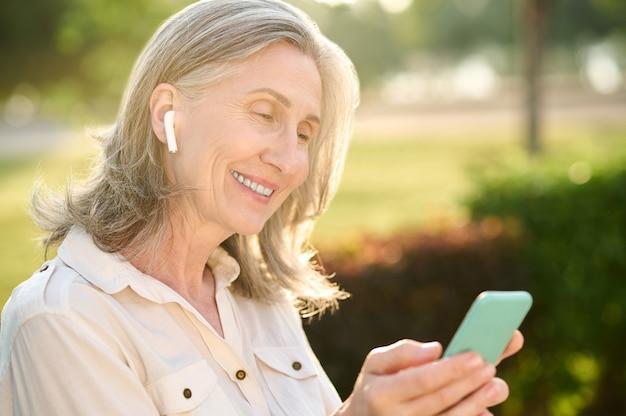 좋은 소식. 스마트폰과 이어폰을 끼고 녹색 공원 벤치에 앉아 있는 잘생긴 성인 백발 성인 여성