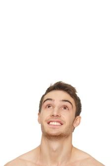良いニュースです。大きく笑っている上のcopyscpaceを見上げている若い幸せな男の垂直ショット
