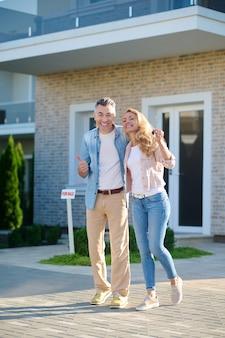 좋은 소식. 화창한 날 새 집 근처에 키가 서 있는 여자와 확인 표시를 보여주는 젊은 성인 웃는 남자