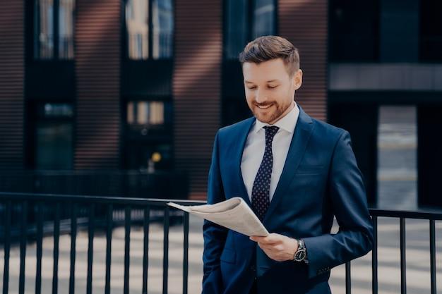 Хорошие новости. молодой богатый прогрессивный владелец фирмы читает газету с улыбкой, стоя перед своим офисным зданием, расслабившись с рукой в кармане, концепция успешных деловых людей