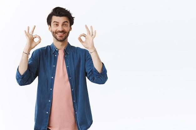 Хороший, хороший выбор. поддерживающий, дружелюбный и счастливый красивый бородатый мужчина что-то оценивает, дает положительный отзыв, показывает хорошо, одобряет и улыбается, согласно кивает, как идея, белая стена