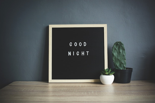 Good night quote on blackboard with cactus and succulent on wooden table