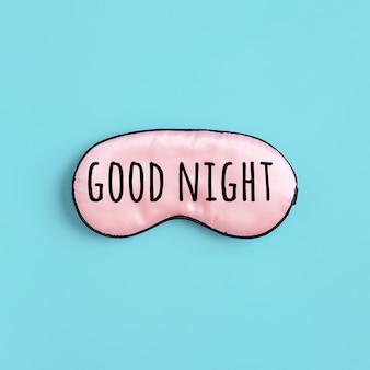 青い背景の目のためのピンクのシルクの睡眠マスクのおやすみテキスト。上面図フラットレイ。良い睡眠とメラトニンのためのコンセプトアイプロテクション