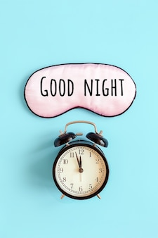 Good night text on pink sleep mask for eyes and black alarm clock on blue background.