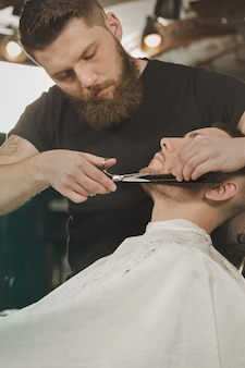 Good old scissors. vertical shot of a barber trimming beard to his client using scissors