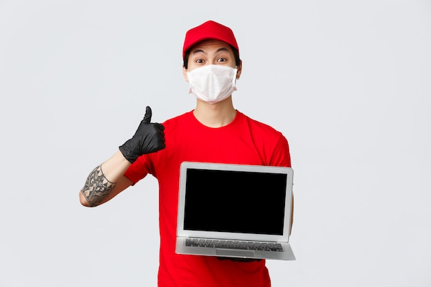 Good online service for food delivery or shopping. cheerful courier in red cap and t-shirt, delivery guy holding laptop, wear medical mask, gloves, thumb-up, recommend contactless deliver of parcel