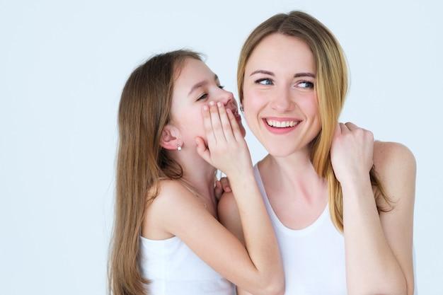 좋은 양육과 사랑의 가족 관계. 그녀의 어머니의 귀에 비밀을 속삭이는 딸.