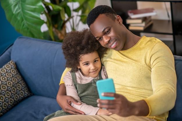 Хорошая фотография. маленькая афро-американская девочка с папой, радостно обнимая друг друга, глядя в смартфон, сидя на диване у себя дома