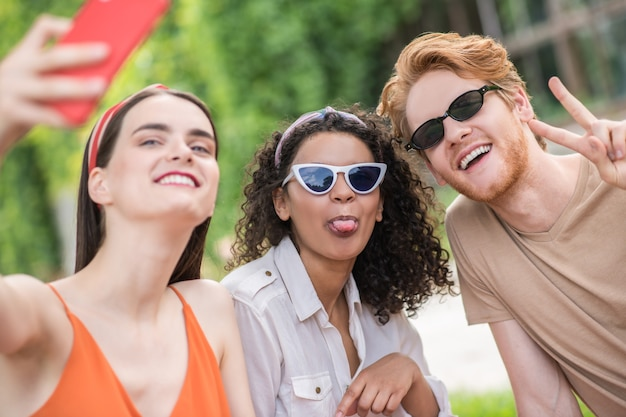Good photo. red-haired guy in sunglasses showing freedom gesture and two cute cheerful girls taking selfie on smartphone outdoors