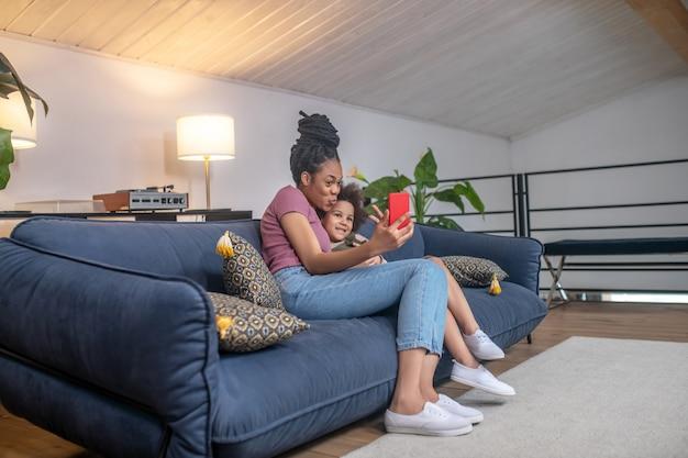 Хорошая фотография. улыбающаяся темнокожая молодая женщина и маленькая милая дочь делают селфи на смартфоне, сидя на диване у себя дома