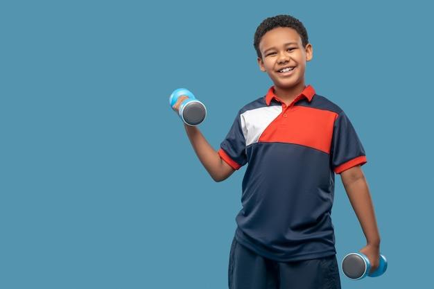 좋은 신체 형태. 파란색 배경에 서 아령으로 스포츠를 하 고 운동복에 즐거운 어두운 피부 소년