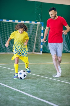 Good player. boy in yellow uniform playing soccer with his coach
