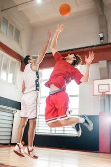 우수한 선수. 빨간 운동복 농구에 생강 남자