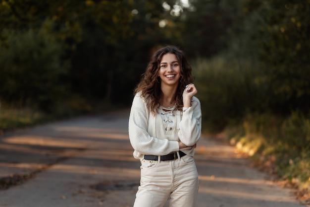 곱슬 머리를 가진 좋은 예쁜 웃는 여자는 야외에서 산책