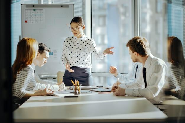 좋은 심리학자. 직원들과 회의를 갖고 그들 사이의 갈등을 해결하려고하는 즐거운 젊은 여성 상사