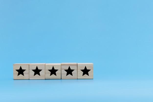 Хорошее качество. значок пяти звезд на деревянном стеке блока куба на синем фоне, отзывы клиентов, творческая идея, бизнес-стратегия, онлайн-маркетинг, позитивное мышление, концепция удовлетворенности клиентов