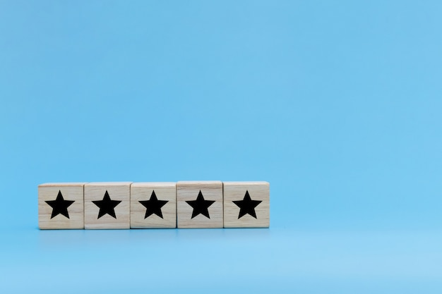 Good quality. five star icon on wooden cube block stack on blue background, customer feedback, creative idea, business strategy, online marketing, positive thinking, customer satisfaction concept