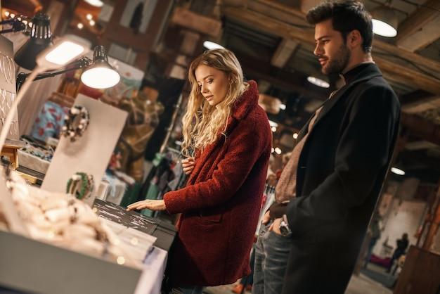 良質の手作りの模造ジュエリー。小さなストリートマーケットで手作りの模造ジュエリーを選ぶ幸せな若い楽しいカップル。秋のシーズン、彼女のボーイフレンドと一緒にブロンドの髪の女性がストリートマーケットにいます