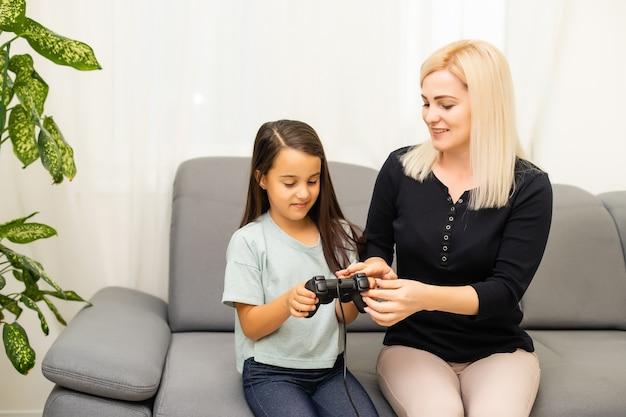 家族の休日を楽しんでいるリビングルームに一緒に座ってビデオゲームをプレイジョイスティックを使用して若い母親との良好な関係かわいい女の子。