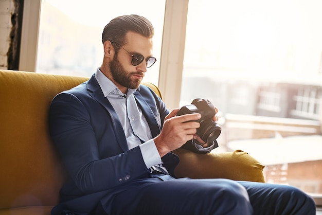 Good result charming young businessman dressed in stylish suit is sitting on sofa and looking