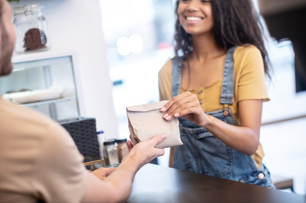 良いサービス。長いウェーブのかかった髪の幸せな女性に小さな紙袋を渡すカウンターの後ろの販売員