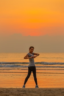 Good shape woman standing and exercise on beanch in the morning with colorful sky in background.