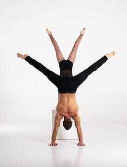 白い背景で隔離逆立ち運動を練習する良い形の男性と女性。強さとモチベーション。