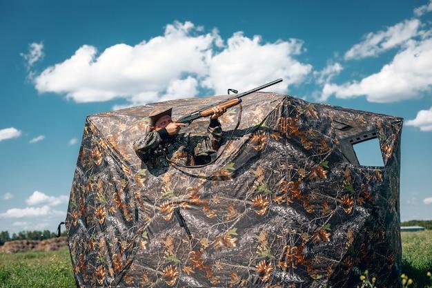 Хороший выстрел стоял в засаде в палатке цвета хаки, целясь в небо; концепция егеря.