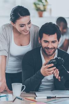 Хорошие кадры! двое коллег обсуждают что-то, пока мужчина держит камеру и улыбается с людьми, работающими на заднем плане