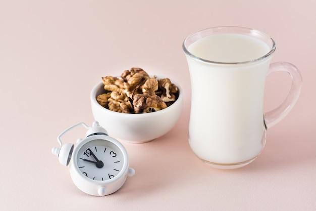 良い睡眠。良い睡眠のための食品-ピンクの背景に牛乳、クルミ、目覚まし時計