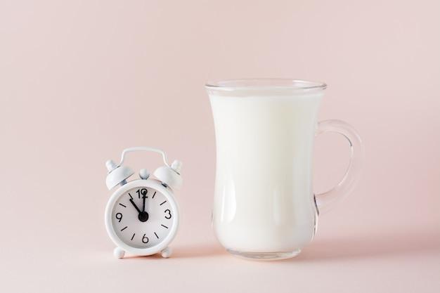 良い睡眠。ピンクの背景に良い眠りと目覚まし時計のための乳製品のガラス