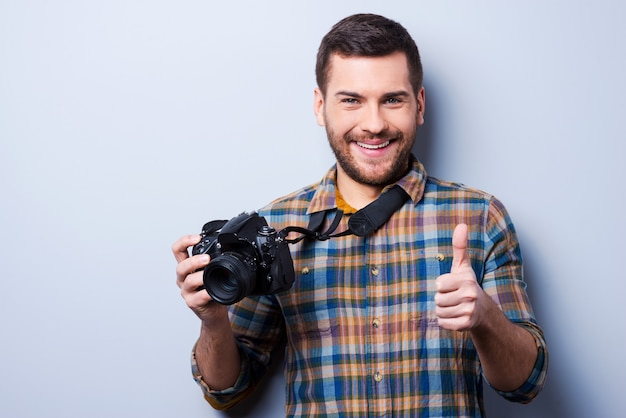Good smile!. portrait of confident young man in shirt holding camera and showing thumb up while standing against grey background