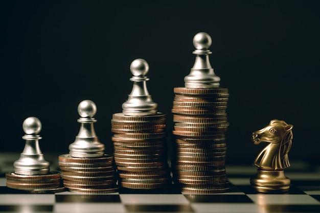 좋은 직원 팀워크 승자 싸움 개념, 기사 말과 함께 쌓인 동전에 작은 폰 체스 조각.